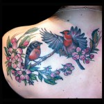 Pair of Robins and apple blossom tattoo colorful floral flowers birds in flight done by female tattoo artist Jessi Lawson